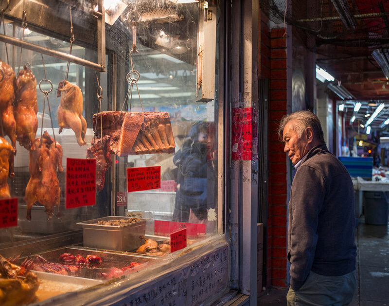 A man is stopped outside a BBQ meats shop in Chinatown while a woman exits the same shop.
