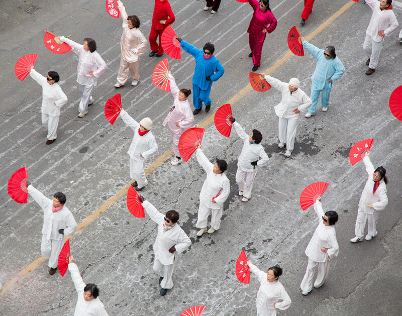 Slightly elevated view of a group of performers with fans as part of a parade in Vancouver's Chinatown