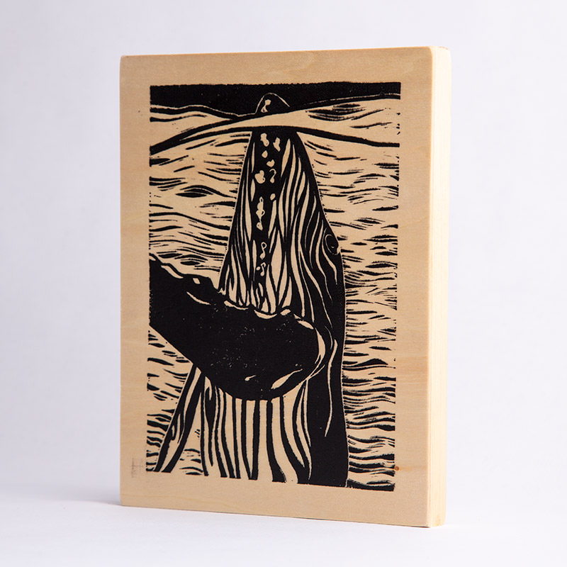 Linocut print on wood panel of a whale illustration