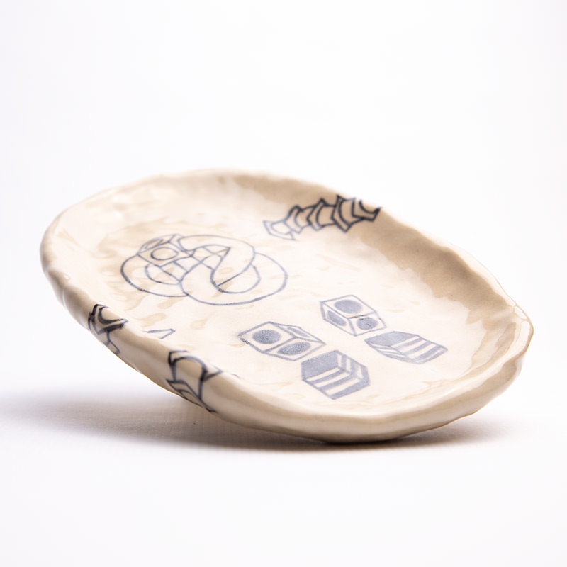Beige coloured ceramic plate with hand-drawn illustrations against a white background